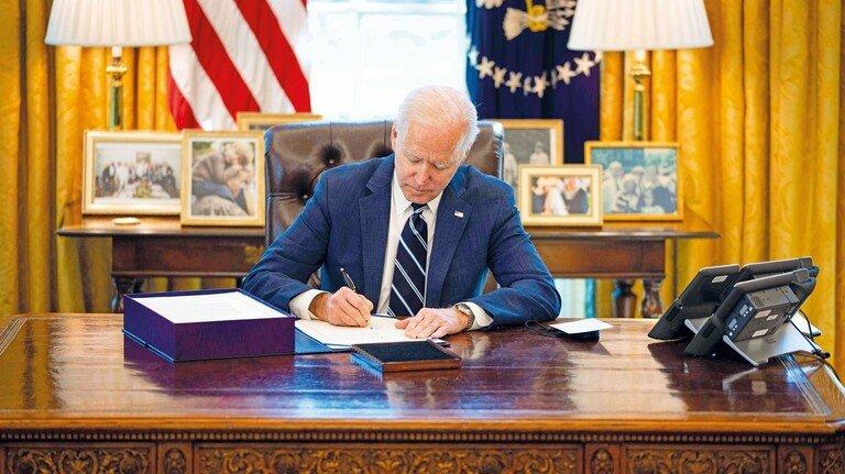 Vor Flaggen und Familienfotos: US-Präsident Joe Biden unterzeichnet das Gesetz zum Konjunkturprogramm.