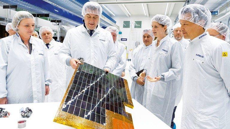 Hoher Besuch: Ministerpräsident Markus Söder begutachtet ein Solarpanel im Reinraum von Airbus.