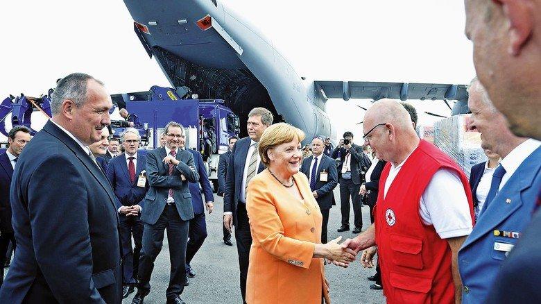 Mehrzweck-Flieger: Die Maschine transportiert auch ziviles Material für Hilfsorganisationen wie das Rote Kreuz - hier ein Bild mit Kanzlerin Angela Merkel.