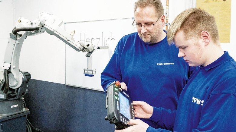 Wissensbegierig: Max Scholl (rechts) mit Ausbilder Markus Petri an einem Roboter.