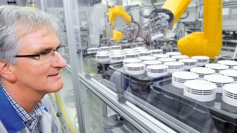 Alle fünf Sekunden ein Gerät: Fertigungsleiter Dietmar Bohn beobachtet einen der Roboter. Foto: Sigwart